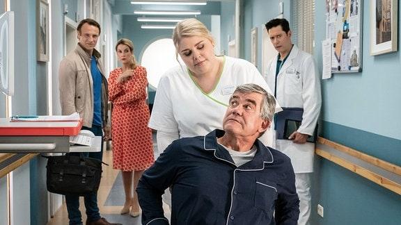Schwester Miriam (Christina Petersen, mi.) schiebt Udo von Wackerstein (Dirk Schoedon, vorn) durch den Klinikgang.