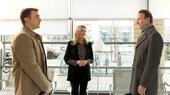 Drei Menschen in Businesskleidung stehen einander gegenüber.