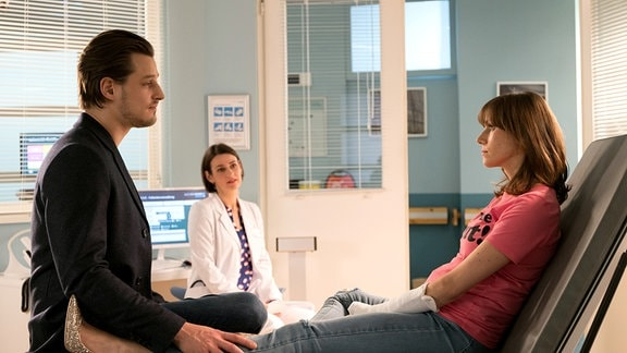 Tessa und ihr Freund Sven sitzen einenander gegenüber. Dr. Maria Weber im Hintergrund.