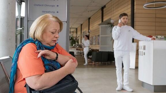 Eine Frau untersucht ihre Wunde