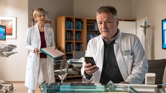 Dr. Heilmann (Thomas Rüchmann) schaut auf sein Handy