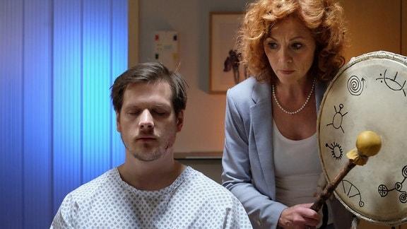 Regina Gerlach (Heike Trinker) führt bei Steffen Hartwig (Enno Hesse) ein Trommelritual zur Stärkung durch. Nur so fühlt sich Steffen für seine bevorstehende OP gewappnet.