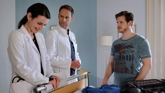 Patient Steffen Hartwig, Dr. Kai Hoffmann und Dr. Maria Weber im Krankenzimmer.
