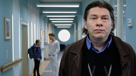 Michael Linse steht im Klinikgang. Im Hintergrund hört er Hanna hinter sich mit Pfleger Kris Haas plaudern.