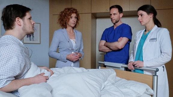 Drei Menschen stehen um ein Krankenbett - Szene aus In aller Freundschaft.