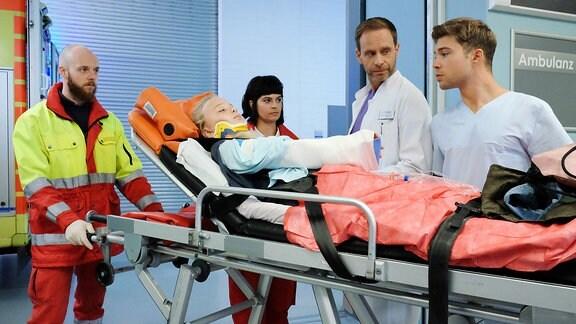 Dr. Kai Hoffmann (Julian Weigend, 2.v.re.) nimmt von der Notärztin (Sarah Arntz, mi.) die kleine Laura Schütz (Lale Andrä, liegend) entgegen.