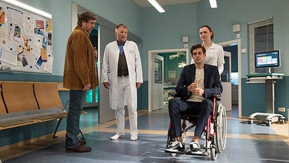 Tim Lennart im Rollstuhl, sein Onkel und Roland Heilmann stehen dabei.