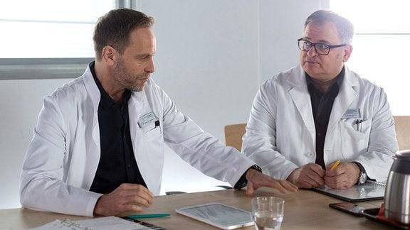 In der Ąrztekonferenz besprechen sich Dr. Kai Hoffmann (Julian Weigend, li.) und Hans-Peter Brenner (Michael Trischan, re.) .