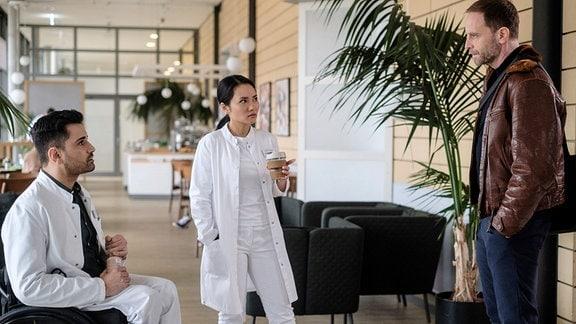 Dr. Kai Hoffmann (Julian Weigend, re.) hat zufällig ein Gespräch zwischen Dr. Lilly Phan (Mai Duong Kieu, mi.) und Dr. Ilay Demir (Tan Çağlar, li.) mitbekommen. Ilay hat Lilly von einem jungen Mann erzählt, der unerlaubt bei seiner Patientin war. Nun hat Dr. Hoffmann einen Verdacht.
