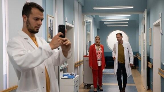 """Dr. Kai Hoffmann (Julian Weigend, re.) und Sarah Marquardt (Alexa Maria Surholt, 2.v.re.) mit einem """"Fan"""" (Komparse, li.)"""