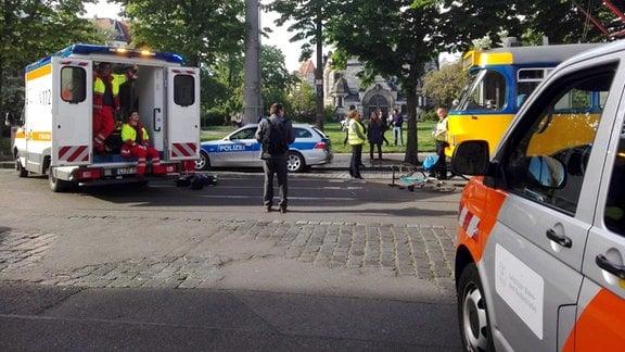 Rettungskräfte in Rettungswagen, Polizeifahrzeug, Straßenbahn