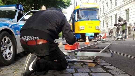 Polizeifahrzeug, Mann mit Leiter, Straßenbahn