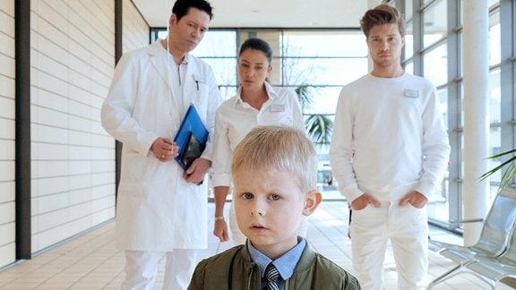 Gerade erst ist der große Sohn von Arzu Ritter (Arzu Bazman, hi. mi.) und Dr. Philipp Brentano (Thomas Koch, hi. li.) operiert worden, als Pfleger Kris Haas (Jascha Rust, hi. re.) mit der nächsten Hiobsbotschaft kommt. Der kleine Sohn der beiden Max (Ben Grünberg, vorn) humpelt.