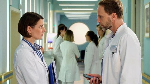 Dr. Maria Weber (Annett Renneberg) muss sich vor ihrem Chefarzt Dr. Kai Hoffmann (Julian Weigend) rechtfertigen, warum sie die PJler betreut und nicht das angeordnete MRT macht. Maria sagt, dass für beides Zeit sei, doch Kai geht die Eigenmächtigkeit seiner Ärzte eindeutig zu weit.