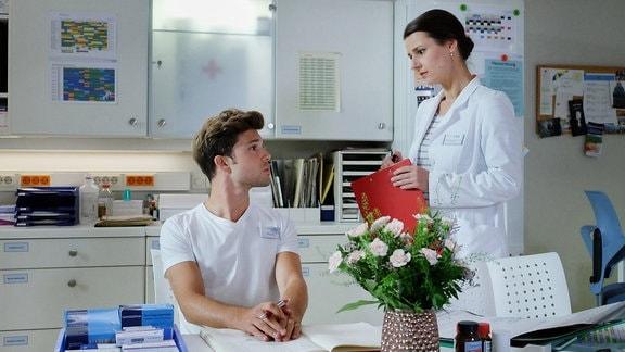 Beim Schichtwechsel bittet Dr. Maria Weber (Annett Renneberg) Kris Haas (Jascha Rust) ein besonderes Auge auf ihre Patientin Alma Bachmann zu haben.