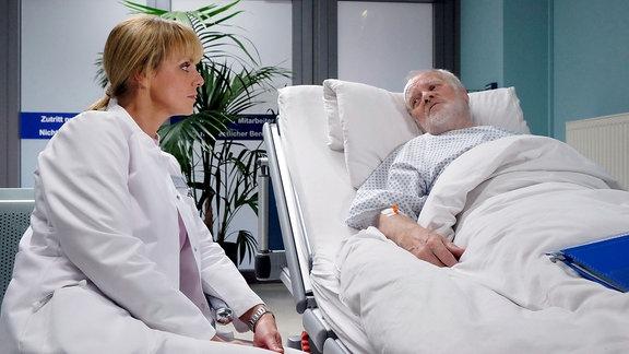 Dr. Lea Peters (Anja Nejarri) sitzt am Krankenbett von Hilger Derbeck (Peter Franke).