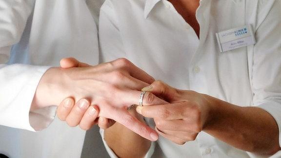 Oberschwester Arzu Ritter (Arzu Bazman, re.) fordert von Dr. Lea Peters (Anja Nejarri, öli.) ihren Ehering zurück. Doch leider geht dieser nicht mehr von Leas Finger ab.