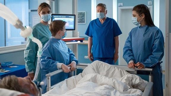 Zwei Frauen, ein Junge und der Arzt am Bett des Patienten.
