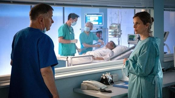 Ein Arzt und eine Frau im Gespräch. Im Hintergrund untersuchen zwei Ärzte einen Patienten.