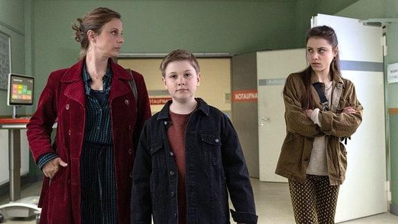 Zwei Frauen und ein Junge in einem Gang des Krankenhauses.