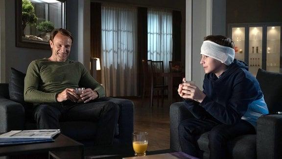 Ein Mann und ein Junge mit verbundenem Kopf sitzen in Sesseln.