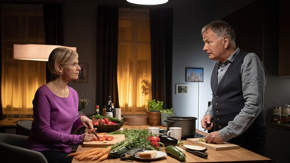 Ein Mann und eine Frau am Küchentisch beim Zubereiten einer Mahlzeit.