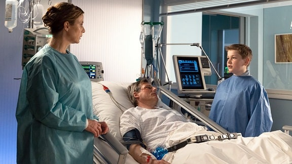 Eine Frau und ein Junge am Krankenbett eines Patienten.