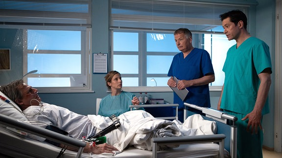 Drei Ärzte stehen um einen Patienten im Krankenbett herum.