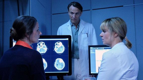 Dr. Maria Weber (Annett Renneberg, li.) spricht über ihre OP mit Dr. Lea Peters (Anja Nejarri, re.) und Dr. Martin Stein (Bernhard Bettermann, mi.).