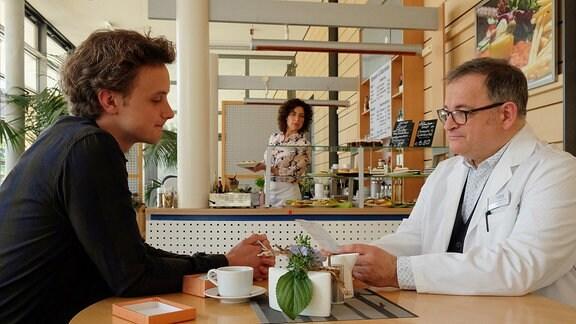 Daniel Gerdes (David Nolden, li.) redet in der Cafeteria mit Hans-Peter Brenner (Michael Trischan, re.).