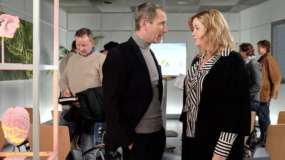 Sarah Marquardt (Alexa Maria Surholt, vorn re.) und Richard Noll (Heikko Deutschmann, vorn li.) haben der Presse (Komparsen im Hintergrund) erfolgreich das Bioprinting-Exzellenzzentrum der Sachsenklinik vorgestellt.