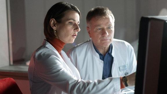 Dr. Maria Weber und Dr. Rolands Heilmann blicken gemeinsam auf den Bildschirm.