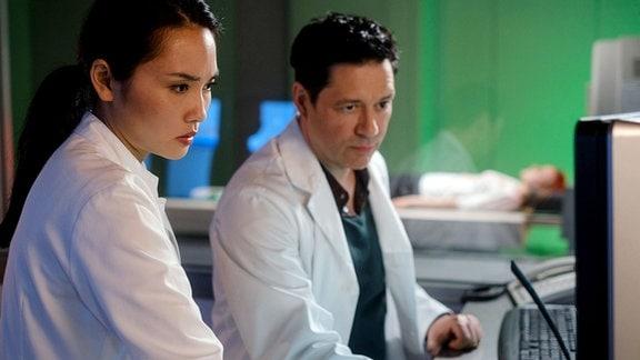 Bei der Erstuntersuchung hat Dr. Philipp Brentano (Thomas Koch) festgestellt, dass Juliane Kling (Sophia Schober, hi.) nicht richtig sehen kann. Gemeinsam mit Dr. Lilly Phan (Mai Duong Kieu, li.) geht er der Sache auf den Grund.