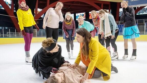 Nachwuchs-Eiskunstläuferin Solveig liegt bewusstlos auf dem Eis. Arzu Ritter und Mutter Jutta helfen.