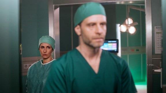 Dr. Weber steht hinter Dr. Hoffmann vor dem OP