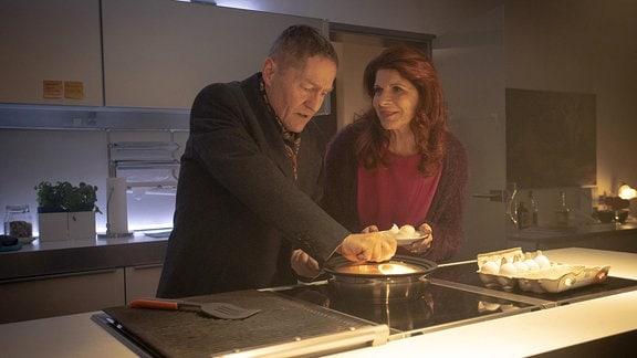 Rolf Kaminski (Udo Schenk) will eigentlich nur nach Vera Bader (Claudia Wenzel) sehen, doch er kommt gerade rechtzeitig. Vera hat eine Pfanne auf dem Herd vergessen, die lichterloh brennt.