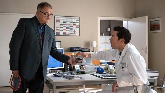 """Dr. Philipp Brentano (Thomas Koch, re.) hat ziemlich schlechte Laune, da der 3D-Drucker kaputt ist und kein Techniker Zeit für eine Reparatur hat. Doch als Hans-Peter Brenner (Michael Trischan, li.) mit """"Muttis"""" Kuchen im Ärztezimmer steht, scheint der Tag gerettet."""