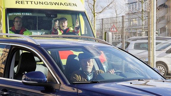 Als Dr. Henrik Oswald (Horst Janson, vorn) nach seinem Termin mit dem Auto wegfahren will, stöߟt er fast mit einem Rettungswagen zusammen.