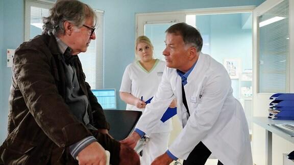 Heinz Rudolph (Andreas Schmidt-Schaller, li.) kommt mit einer Knieverletzung in die Sachsenklinik. Dr. Roland Heilmann (Thomas Rühmann, re.) untersucht ihn.