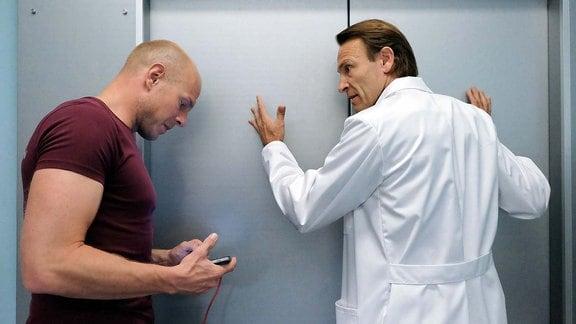Dr. Martin Stein (Bernhard Bettermann, re.) steht hilflos am Fahrstuhl in dem gerade eine seiner Patientinnen um ihr Leben kämpft.