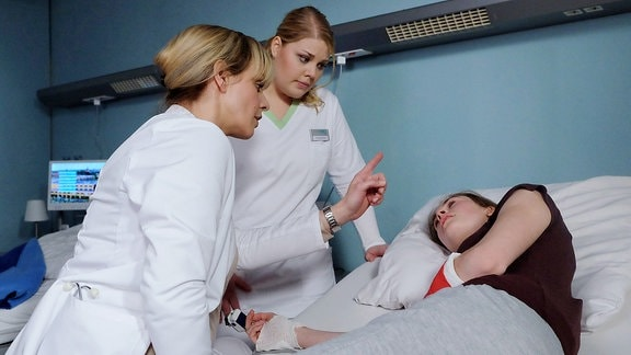 Frida Semmler (Pauline Ränevier, re.) verweigert eine lebensnotwendige Operation. Die 16-Jährige war mit neune Jahren schon drogenabhängig und nun hat sie Angst, von der Narkose rückfällig zu werden. Als Schwester Miriam (Christina Petersen, mi.) in Fridas Zimmer kommt, kann sie fast nichts mehr sehen. Dr. Lea Peters (Anja Nejarri, li.) ordnet ein sofortiges CT an, doch sie weiß, dass eine OP unumgänglich ist.