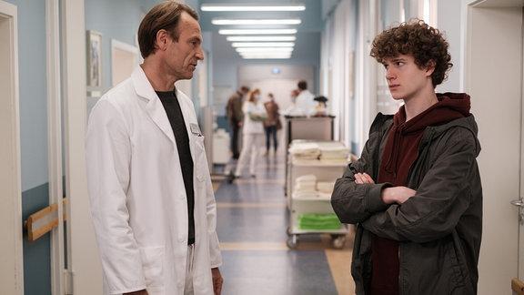 Dr. Martin Stein (Bernhard Bettermann, li.) spricht mit dem jungen Lukas im Gang.