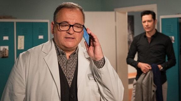 Dr. Philipp Brentano (Thomas Koch, re.) hört ganz zufällig ein Telefongespräch seines Freundes und Kollegen Hans-Peter Brenner (Michael Trischan, li.) mit. Für Philipp hört es sich eindeutig so an, als würde Hans-Peter mit einer Frau telefonieren. Philipp freut sich für seinen Freund.