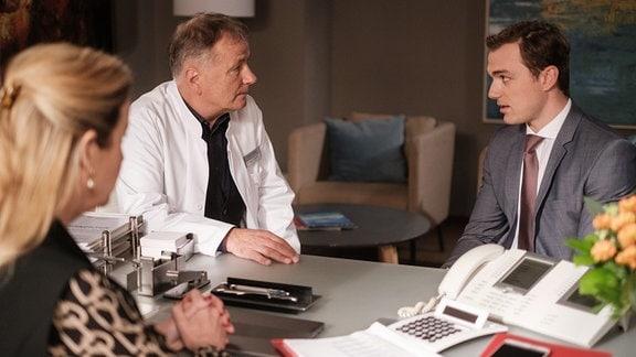 Dr. Roland Heilmann (Thomas Rühmann, mi.) muss sich vorm Gesundheitsdezernenten Dr. Clemens Seidel (Moritz von Zeddelmann, re.) rechtfertigen.