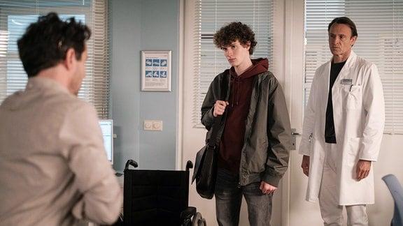 Ingo Mischke (Christian Schmidt, li.) ist sauer, dass sein Sohn Lukas (Nico Ramon Kleemann, mi.) ihn in die Sachsenklinik gelockt hat. Sie sprechen mit Dr. Stein.
