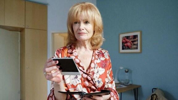 Karla Stadlmannn (Gertie Honeck) hält ein Foto in der Hand.