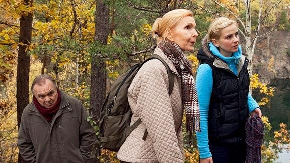 Oberschwester Ingrid, Prof. Simoni und Hobbykletterin Isabel Dahl im Wald.