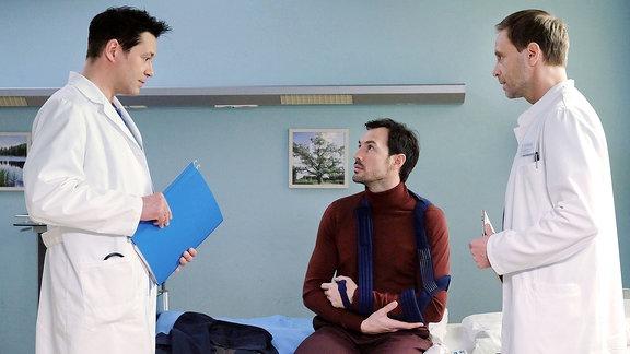 Zwei Ärzte sprechen mit einem Mann, der den Arm in einer Schlinge trägt.