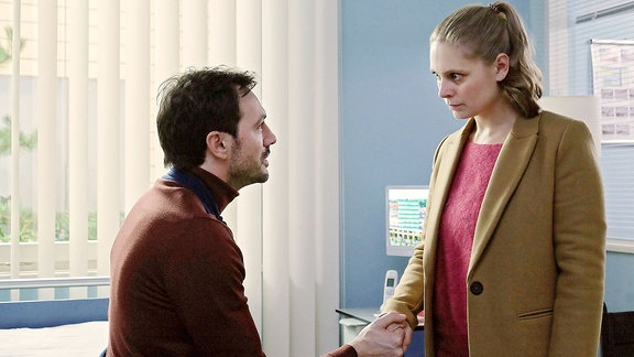 Ein Mann begrüßt sitzend eine Frau.