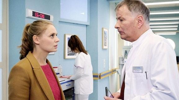 Auf einem Krankenhausflur spricht eine Frau mit einem Arzt.